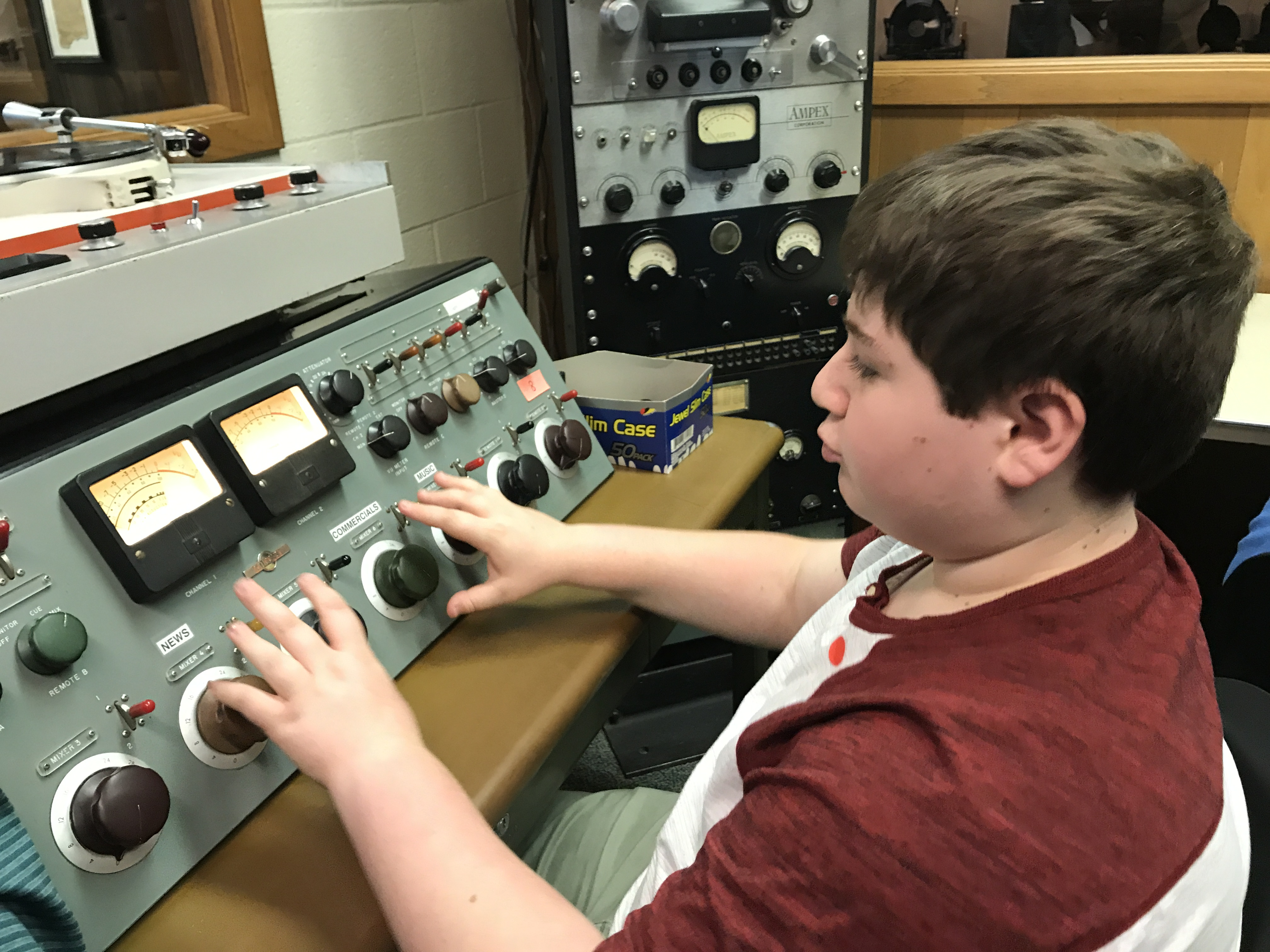 8th Grader experiments with old broadcasting equipment on field trip to Pavek Museum